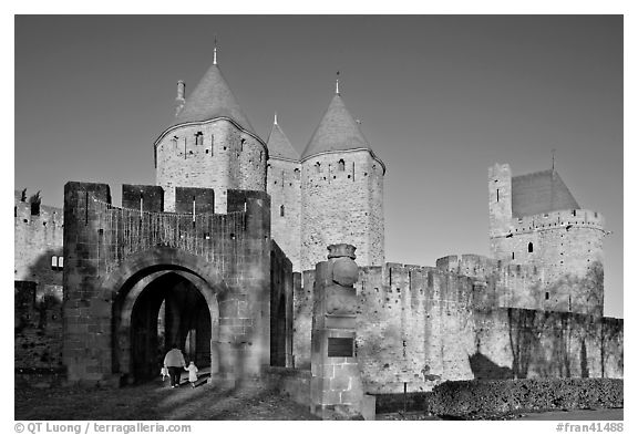 Main entrance of medieval city  with child and adult walking in. Carcassonne, France (black and white)