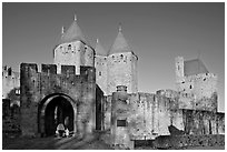Main entrance of medieval city  with child and adult walking in. Carcassonne, France ( black and white)