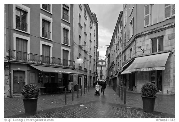 Pedestrian street with couple pushing stroller. Grenoble, France (black and white)