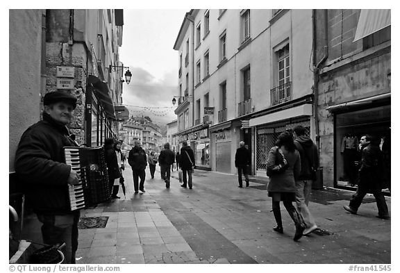Accordeon musician on commercial pedestrian street. Grenoble, France (black and white)