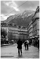 Downtown street and snowy mountains of the Belledone Range. Grenoble, France (black and white)