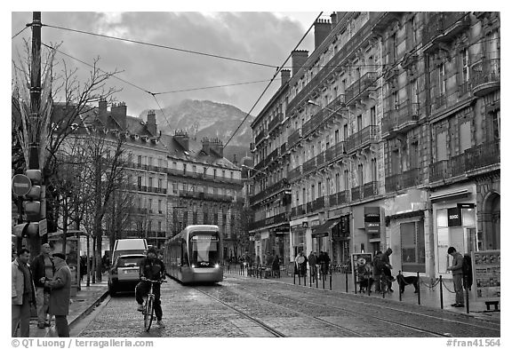 Bicyclist and tramway next to Victor Hugo place. Grenoble, France (black and white)