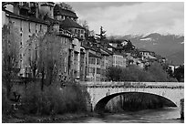 Stone bridge, houses, and snowy mountains. Grenoble, France (black and white)