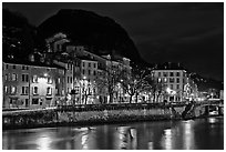 Isere River and houses below the Citadelle at night. Grenoble, France (black and white)