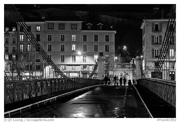 Pedestrians on suspension bridge at night. Grenoble, France (black and white)