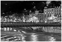 Suspension bridge at night with Christmas lights reflected in river. Grenoble, France ( black and white)