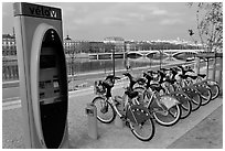 Bicycles for rent with automated kiosk checkout. Lyon, France ( black and white)