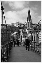 Walking across the passerelle Saint-Georges. Lyon, France (black and white)