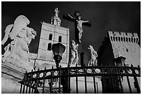 Cross with Christ, statues, and towers, evening light. Avignon, Provence, France (black and white)