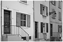 Facade of townhouses with colorful shutters. Arles, Provence, France ( black and white)