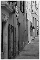 Painted facades in narrow street. Arles, Provence, France (black and white)