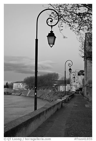 Walkway on the banks of the Rhone River at dusk. Arles, Provence, France
