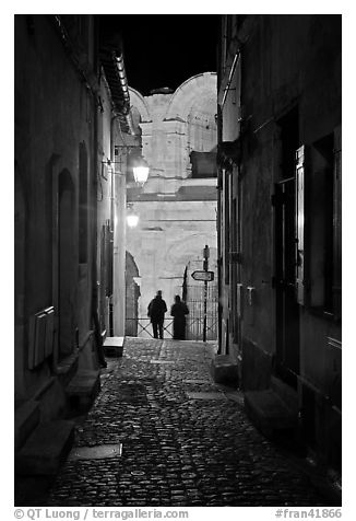Narrow cobblestone passageway at night next to arena. Arles, Provence, France (black and white)