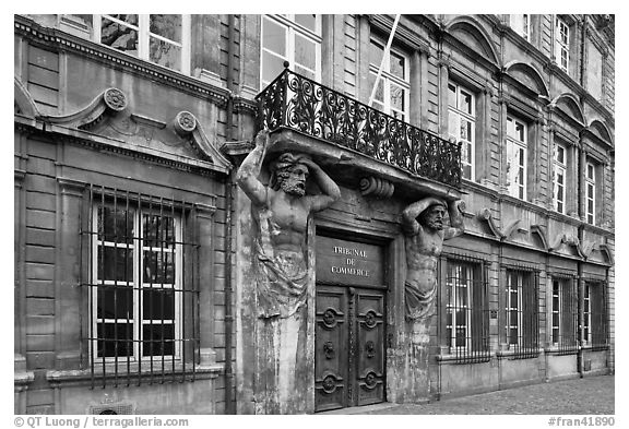 Facade with sculptures supporting a balcony. Aix-en-Provence, France (black and white)