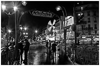 Metro entrance, boulevard, and Moulin Rouge on rainy night. Paris, France (black and white)