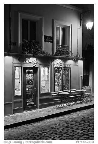 Restaurant with red facade and cobblestone street by night, Montmartre. Paris, France (black and white)