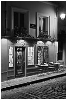 Restaurant with red facade and cobblestone street by night, Montmartre. Paris, France ( black and white)