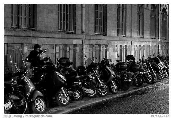 Scooters parked on a sidewalk at night. Paris, France