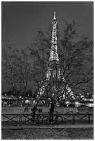 Bicyclists and Eiffel tower at night. Paris, France ( black and white)