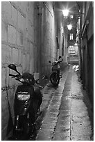 Motorcycles parked in narrow alley at night. Quartier Latin, Paris, France (black and white)