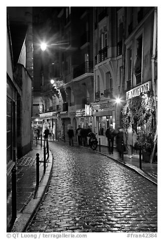 Cobblestone street with restaurants by night. Quartier Latin, Paris, France (black and white)