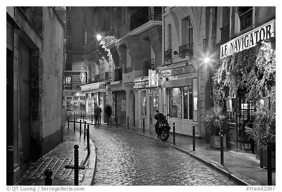 Street with cobblestone pavement and restaurants by night. Quartier Latin, Paris, France (black and white)