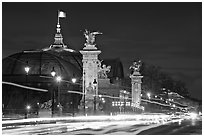 Petit Palais and trafic across Alexandre III bridge by night. Paris, France (black and white)
