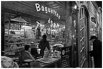 Elderly man entering bakery with people inside. Paris, France (black and white)