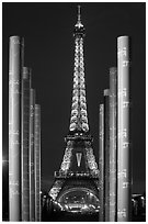 Columns of memorial to peace end Eiffel Tower by night. Paris, France (black and white)