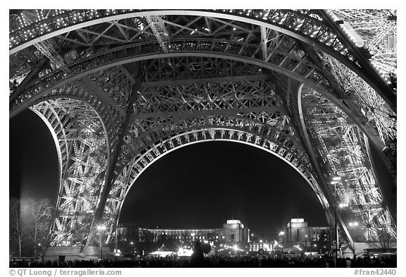 Palais de Chaillot seen through the base of Eiffel Tower by night. Paris, France (black and white)
