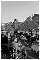 Couple sitting on terrace in Louvre main courtyard. Paris, France (black and white)