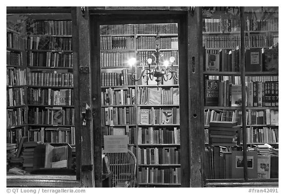 Black and white picture photo books on shelves seen through storefront quartier latin paris france