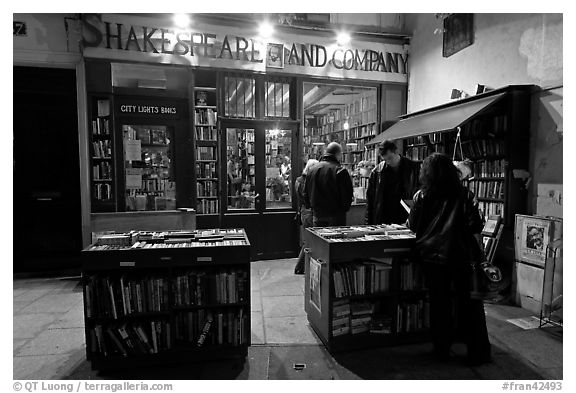 People reading in front of bookstore at night. Quartier Latin, Paris, France (black and white)