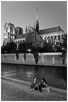 Two women having picnic across Notre Dame cathedral. Paris, France (black and white)
