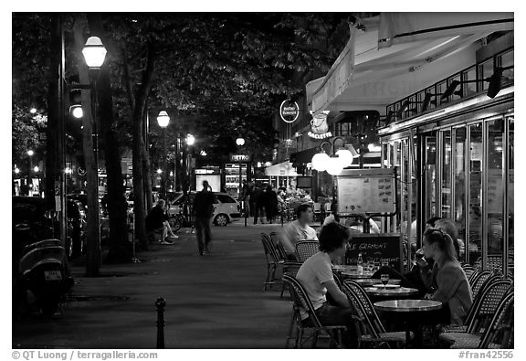 Outdoor cafe terrace on the Grands Boulevards at night. Paris, France (black and white)