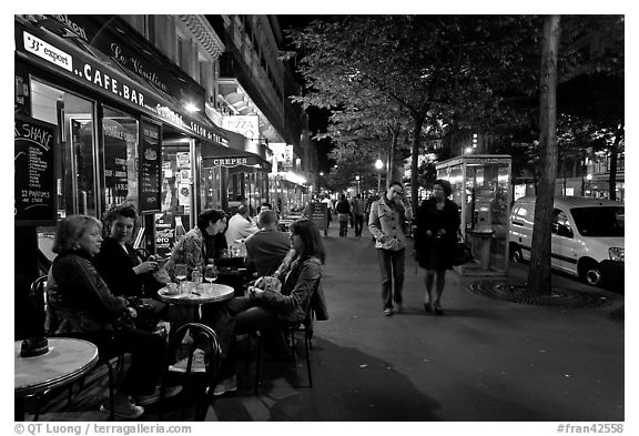 Cafe bar on sidewalk of a Grand Boulevard at night. Paris, France (black and white)