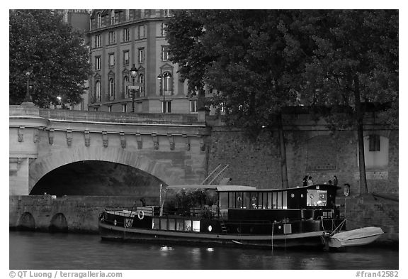 Lighted live-in barge, quay, and Pont-Neuf. Paris, France (black and white)