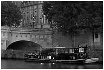 Lighted live-in barge, quay, and Pont-Neuf. Paris, France ( black and white)