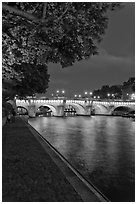 Ile de la Cite quay and illuminated Pont-Neuf. Paris, France (black and white)