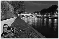 Couple sitting on quay on banks of the Seine River. Paris, France (black and white)
