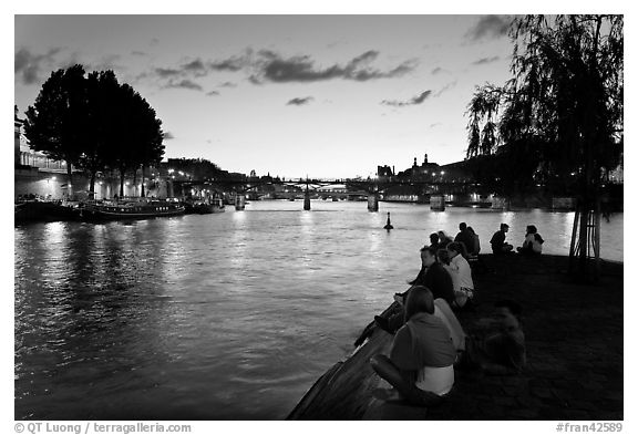 People sitting on tip of Ile de la Cite at sunset. Paris, France (black and white)