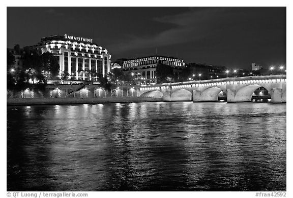 Pont Neuf and Samaritaine reflected in Seine River at night. Paris, France (black and white)