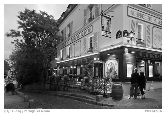 Couple looking at menu outside restaurant, Montmartre. Paris, France (black and white)