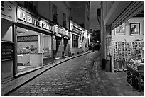 Narrow cobblestone street and businesses at night, Montmartre. Paris, France ( black and white)