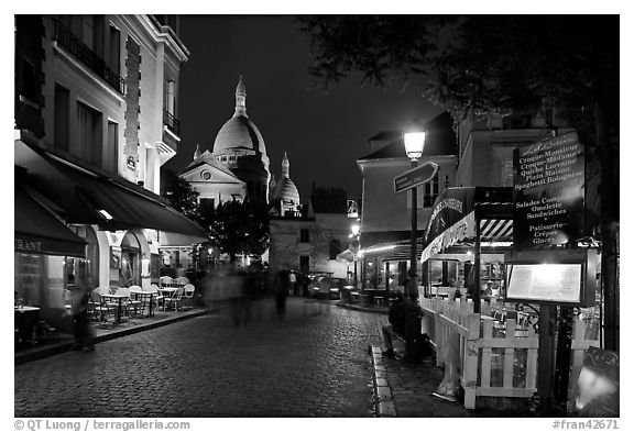 Place du Tertre at night with restaurants and Basilique du Sacre-Coeur, Montmartre. Paris, France (black and white)