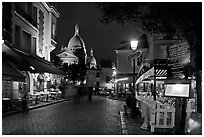 Place du Tertre at night with restaurants and Basilique du Sacre-Coeur, Montmartre. Paris, France ( black and white)