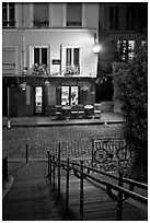 Hillside stairs on butte, street and restaurant at night, Montmartre. Paris, France (black and white)