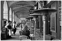 Outdoor cafe tables and heating lamps, place des Vosges. Paris, France (black and white)
