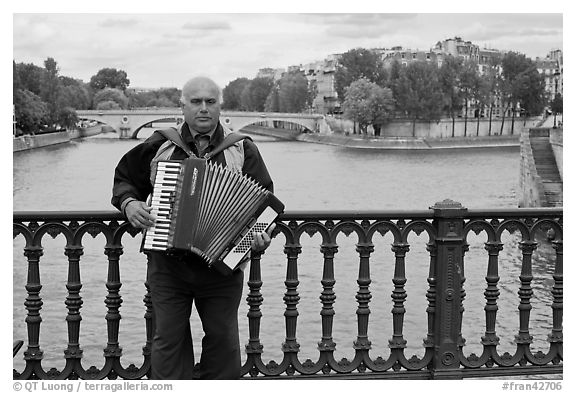 Street musician playing accordeon on River Seine bridge. Paris, France (black and white)