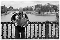 Street musician playing accordeon on River Seine bridge. Paris, France ( black and white)